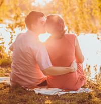 Ein junges Paar küsst sich bei Sonnenuntergang - So werden aus Singles Liebende.